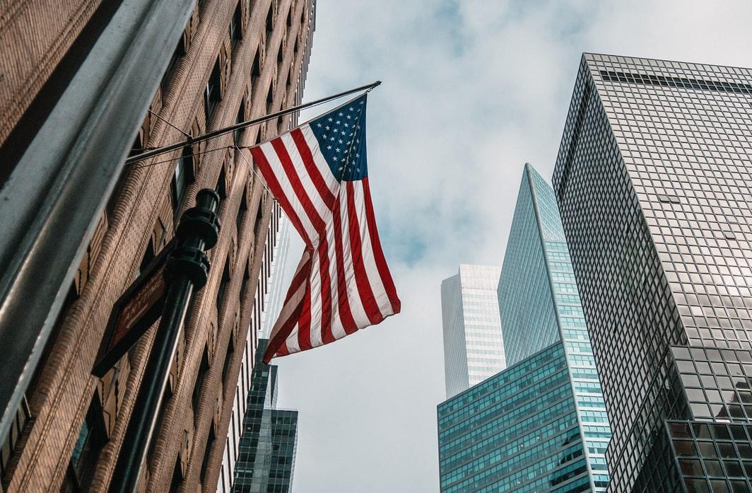 An American flag flying between skyscrapers.