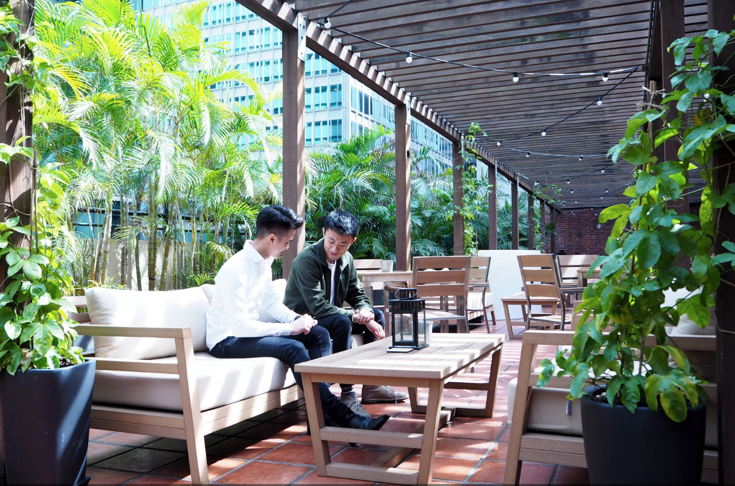 Two men in Singapore sitting outdoors at a coworking space.